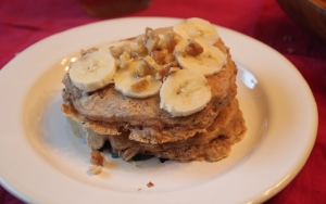 This is two pancakes, layered with bananas and chopped walnuts.