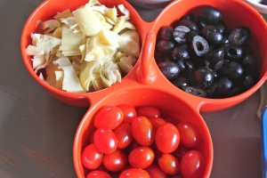 Chopped artichoke hearts, cherry tomatoes, and sliced black olives.