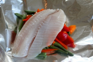 Add one of your tilapia filets on top of your veggies.